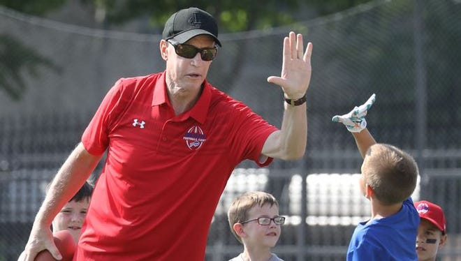 Jim Kelly high-fives Nic Distasio, 9, of Spencerport after catching a pass last week at Kelly's football camp for kids at St. John Fisher College.