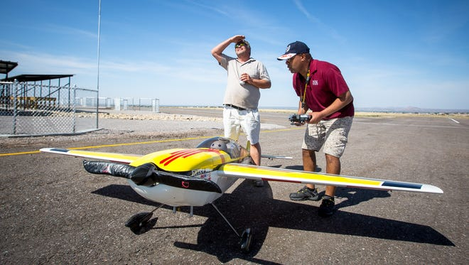 Ken Brouhard left, watches a remote controlled airplane in flight while Fred Upshaw prepares his plane for takeoff during the new Model Airplane and Archery Facility opening, April 22, 2016.