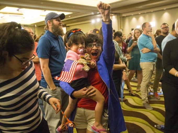 Irma Perez, holding her granddaughter, celebrates at