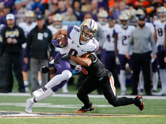 Washington wide receiver Dante Pettis (8) breaks out of a tackle after making a catch in the first half of an NCAA college football game against Oregon State, in Corvallis, Ore., Saturday, Sept. 30, 2017. (AP Photo/Timothy J. Gonzalez)