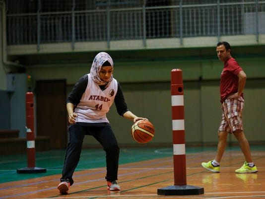 Hacer Sahil, 31, an amateur basketball player trains as her coach Ata Turk watches, right, in Istanbul, Thursday May 4, 2017. Basketball enthusiasts around the world said a decision international basketball's governing body, known as FIBA, to allow players to wear religious headgear in competition will encourage more people to play the sport because it gives participants the right to practice their faith and focus on playing ball. (AP Photo/Lefteris Pitarakis)