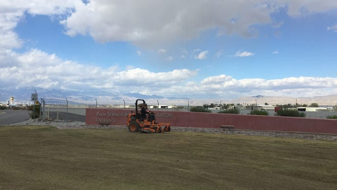 Lawn workers mow the grass near the entrance to Palm Springs International Airport to prepare the area for annual re-seeding which replaces the summer Bermuda grass with winter rye.