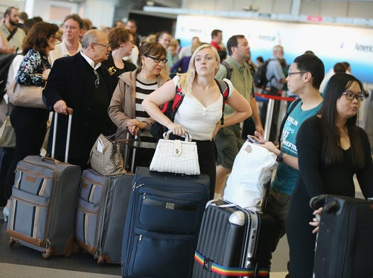 Passengers wait in line to reschedule flights at O'Hare International Airport in Chicago.  All flights in and out of Chicago's O'Hare and Midway airports were halted because of a suspected arson fire at a suburban Chicago air-traffic control facility.