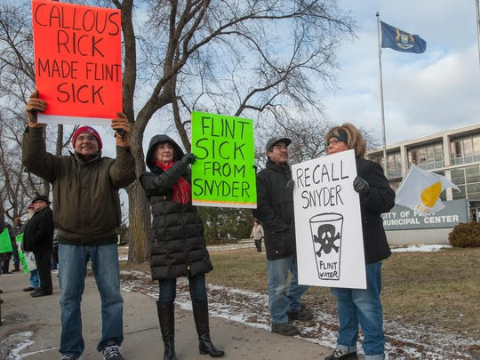Protestors gathered outside of the Flint City Hall on Saturday, January 16, 2016, with Flint native Michael Moore.