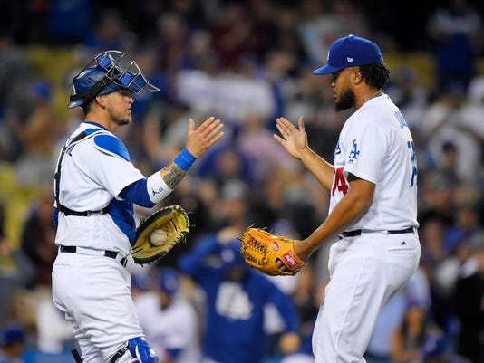 Los Angeles Dodgers relief pitcher Kenley Jansen, right, is congratulated by catcher Yasmani Grandal after the Dodgers defeated the Colorado Rockies 4-2 in a baseball game, Wednesday, April 19, 2017, in Los Angeles. (AP Photo/Mark J. Terrill)