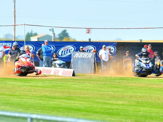 Snowmobiles race on the grass during the 2013 Trailmates Snowmobile Club event in the town of Stettin.