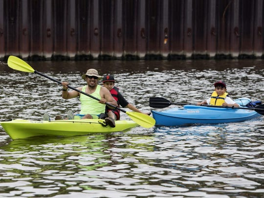 Freddy Herandez Castro (left) kayaks on the Milwaukee River with his nephews Moses (center) and Daniel Jr. Ramirez (right).