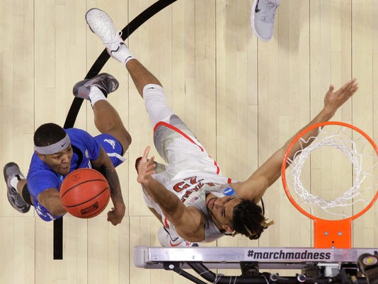 Buffalo guard Wes Clark, left, shoots as Arizona forward Keanu Pinder defends during the first half of a first-round game in the NCAA men's college basketball tournament Thursday, March 15, 2018, in Boise, Idaho. Buffalo won 89-68. (AP Photo/Otto Kitsinger)