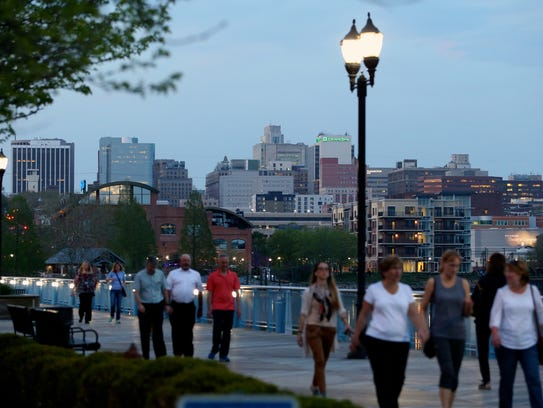 People stroll on the Riverwalk along Wilmington's Riverfront.