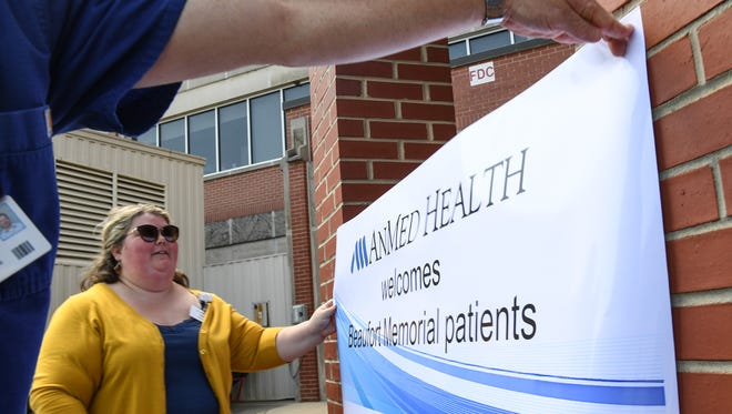 AnMed Hospital Marketing Department employee Tara Stone helps put up a welcome sign for Beaufort hospital patients arriving from an emergency evacuation to AnMed Hospital in Anderson on Friday.
