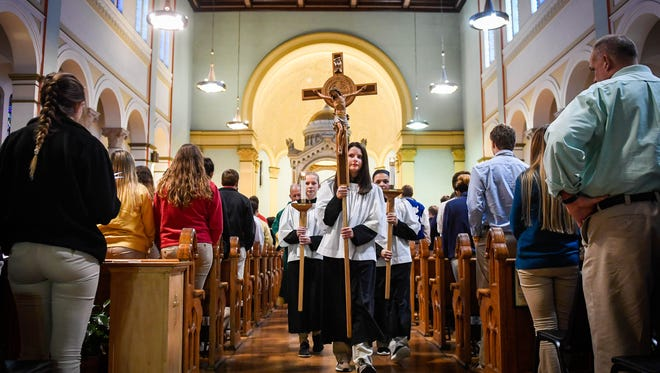 Saint Benedict Cathedral School student Josée Gibson leads the procession out of the Saint Benedict Cathedral following a Mass celebrating National Schools Week Tuesday, January 30, 2018.