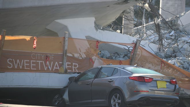 A car is seen stuck under the rubble as law enforcement and members of the National Transportation Safety Board investigate the scene where a pedestrian bridge collapsed a few days after it was built over southwest 8th street allowing people to bypass the busy street to reach Florida International University on March 16, 2018 in Miami.