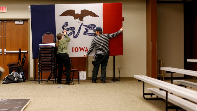 Workers remove an Iowa flag after a town hall featuring Democratic presidential candidate Hillary Clinton at the Toledo Civic Center in Toledo, Iowa, Monday, Jan. 18, 2016.