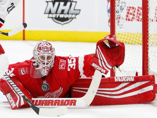 Red Wings goaltender Jimmy Howard (35) attempts to make a save against Hurricanes center Elias Lindholm (28) during the third period of the Wings' 3-1 loss on Saturday, Jan. 20, 2018, at Little Caesars Arena.