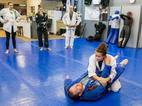 Jackie Bruce demonstrates a reversal maneuver on Bill Walters during a women's self-defense class at 302 Brazilian Jiu-Jitsu in Wilmington on Tuesday night.