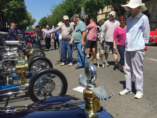 Hundreds walked up and down the streets of downtown Visalia Saturday for the 27th annual Visalia Breakfast Lions car show. Pictured, attendees stop and look at hot rods mixed in with a line of Ford and Chevy cars and trucks.