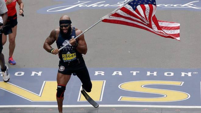 Retired US Marine Staff Sgt. Jose Sanchez, of San Antonio, Texas, carries the United States flag across the finish line in the 121st Boston Marathon on Monday, April 17, 2017, in Boston. (AP Photo/Charles Krupa)