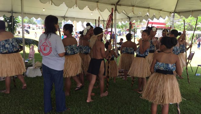 Dancers from Vicente S.A. Benavente Middle School's Guma Taotao Lagu rest in the shade during the 28th Annual Guam Micronesia Island Fair June 12.