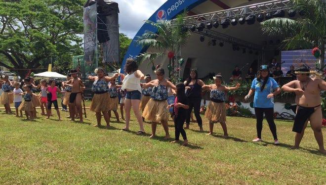 Guma Taotao Lagu from Vicente S.A. Benavente School gets the crowd involved during an encore performance at the 28th Annual Guam Micronesia Island Fair June 12.