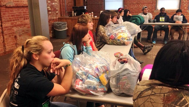 Rapides High School students learn about the Central Louisiana Homeless Coalition and how the 36 kits they prepared will help people in this area.