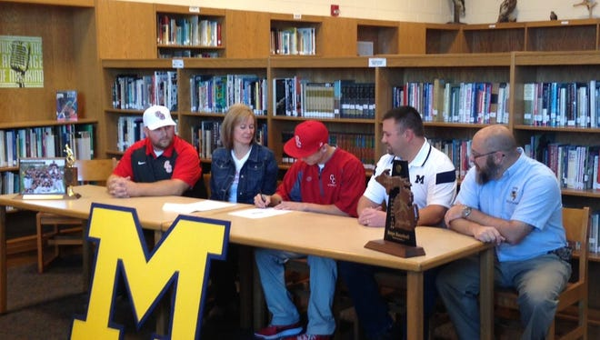 Surrounded by his parents, coach and athletic director, Dillon Mitchell signs his Letter of Intent to play baseball at Olivet College