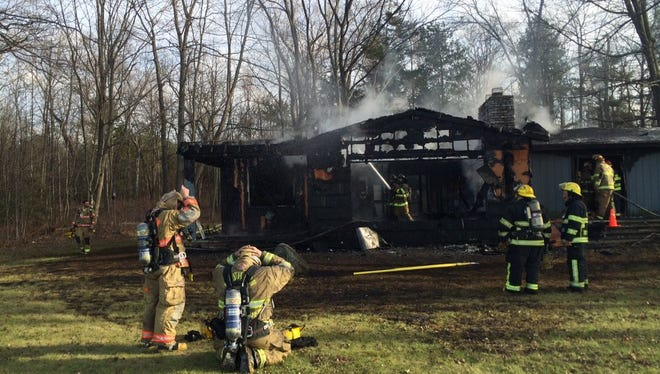 Firefighters hose down hot spots after putting out a blaze at 1381 Bay Shore Drive in the town of Union on Tuesday.