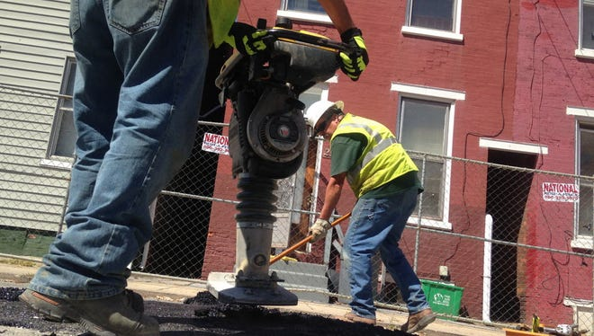 Frank Pugols, left, of Columbia Gas, uses a tamper to patch a hole in the 200 block of Chestnut Street in York. At right, Duain Houck of Columbia Gas, sweeps debris.