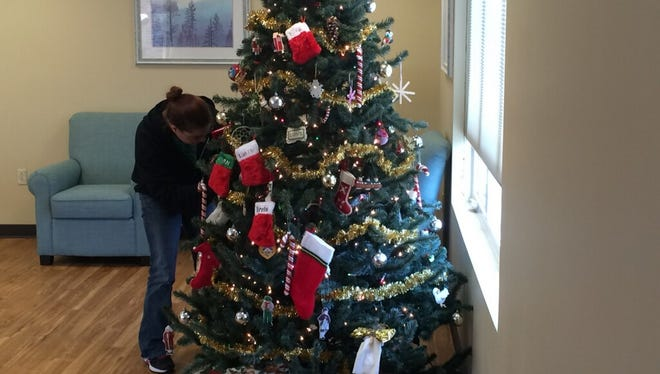 A resident at the Manitowoc County Domestic Violence Center decorates a tree for the shelter.