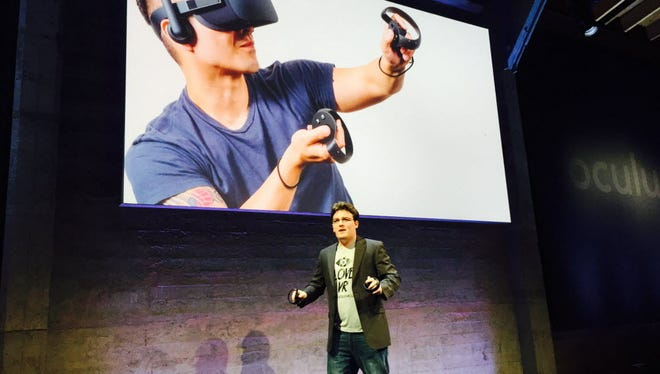 Palmer Luckey shows off Oculus Touch controllers at a news conference in October.