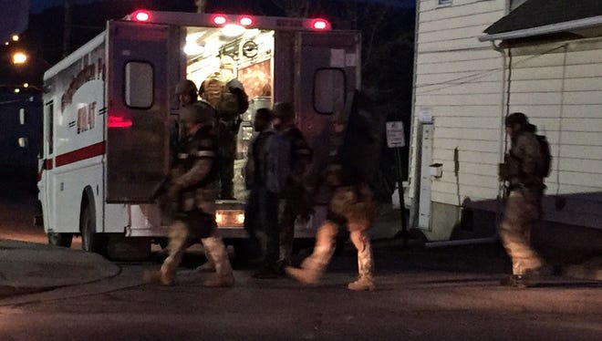 SWAT teams lead out Terry A. Ketchatcham, 27, in handcuffs from the Johnson City residence where he barricaded himself in Friday morning.