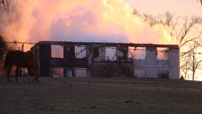 A horse grazes near a home that was destroyed by a fire early Thursday morning in Mount Solon.