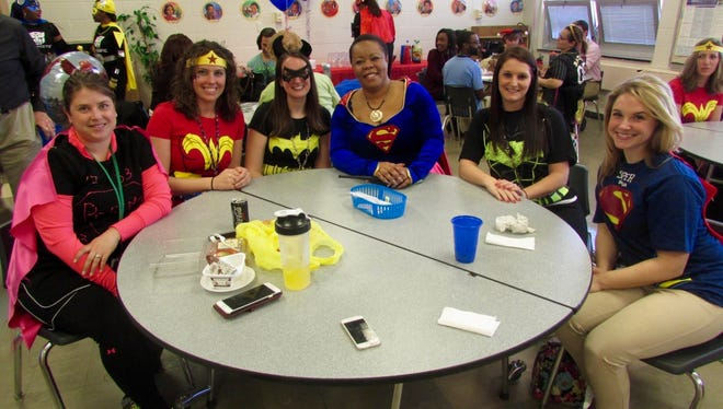 """Winslow Township Middle School staff, including principal Stella Nwanguma (center, wearing a Superman costume) celebrated """"Dress Like A Champion Day,"""" on March 8."""