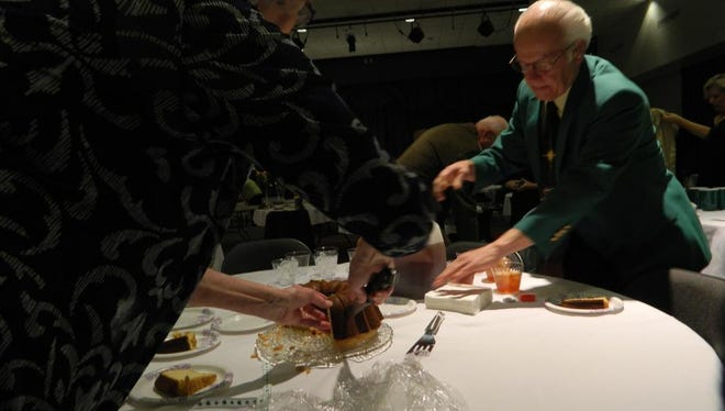 Elizabeth Martin, left, cuts pieces of a cream cheese pound cake that was bought at auction for $1,000, with the help of 2015 Lord High Mayor Bro. Richard Neal, right.