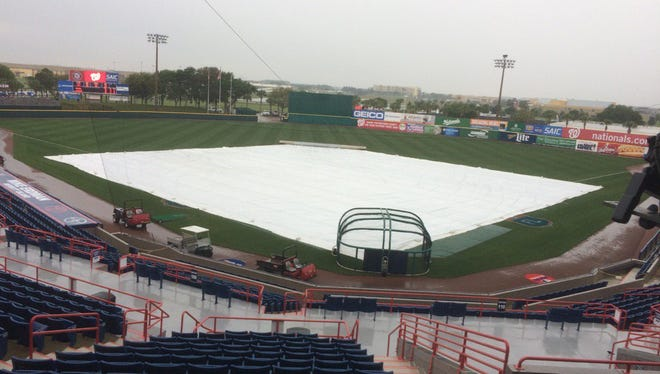 Rain is falling at Space Coast Stadium on Monday.