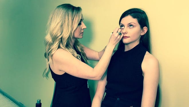 Makeup artist applies eyeliner to model at the KDF Fashion Show.
