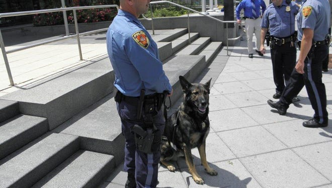 An N.J. Transit Police officer and his K-9 stand at the Trenton Transportation Center.