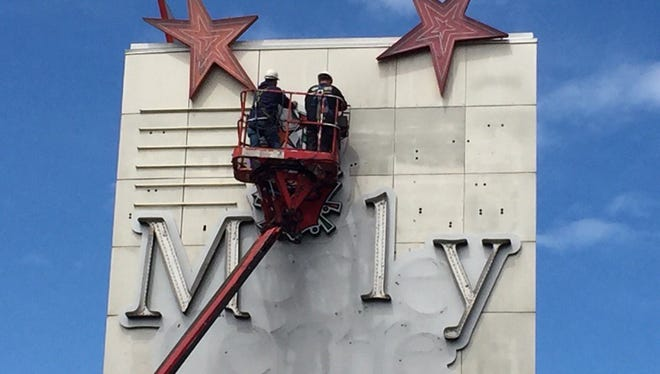 Jeff Sherwood and Drew Goodwin, of Premier Sign Systems, remove the letters and stars from the Medley Centre sign Friday.