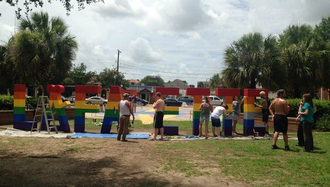 Volunteers paint the Lafayette sign in Parc Sans Souci Tuesday, in honor of the 49 people killed in a mass shooting in Orlando Sunday.