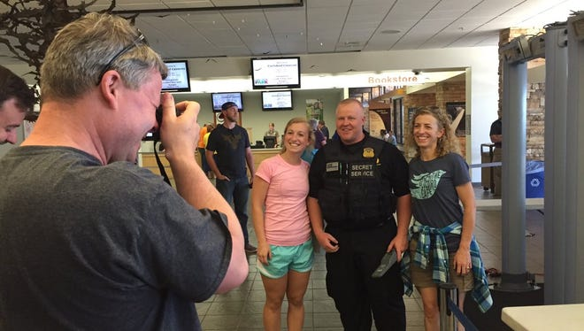 Jim Blundell takes a photo as his daughter, Natalie Blundell, left, and wife Catherine Blundell, right, pose with a Secret Service agent after entering Carlsbad Caverns National Park ahead of the first family's visit Friday.