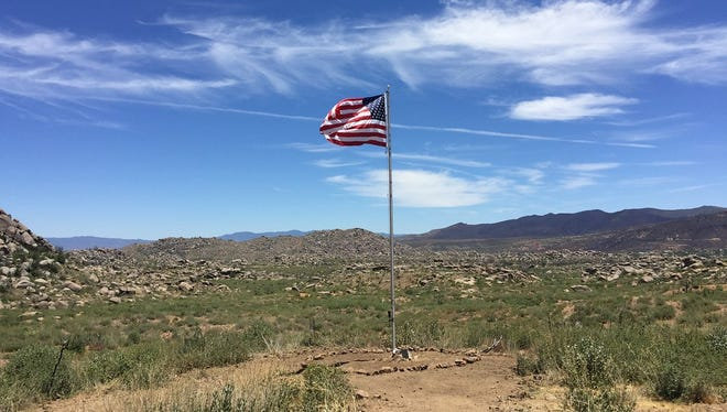 An American flag stands near the site where 19 members of the Granite Mountain Hotshots died on June 30, 2013 in the Yarnell Hill Fire. The state is developing a memorial park on the site.