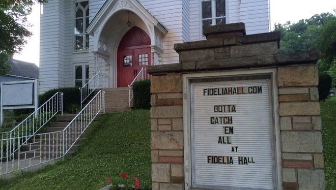 Justin Hoenke, 36, of Titusville, Pa., posted a welcome sign for Pokémon Go players in front of Fidelia Hall, an old church he repurposed into an arts center.
