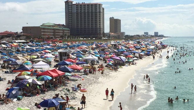 The crowd enjoys the surf and sand while waiting on Pensacola Beach for the Blue Angels.