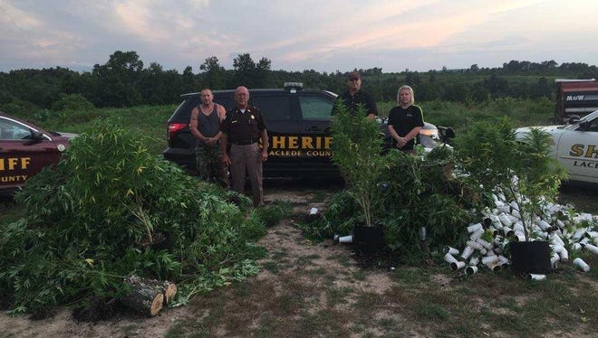 Members of the Laclede County Sheriff's Office pose in front of marijuana seized on Wednesday.