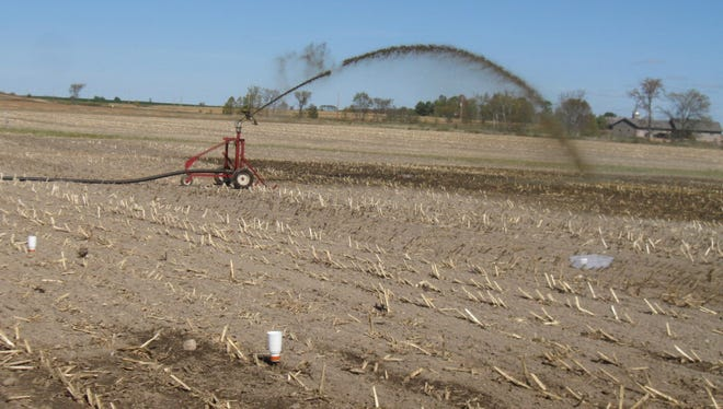 Manure is being applied via an irrigation system using a traveling gun and reel.