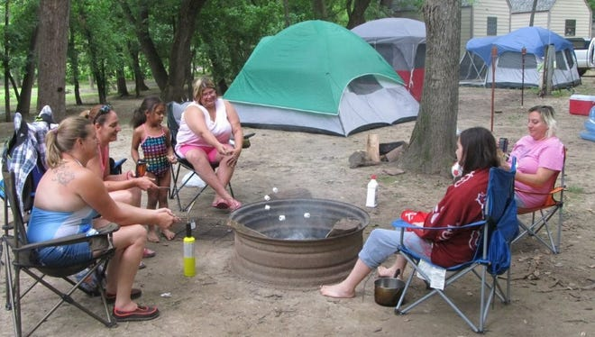 A group of campers from Springfield and Fair Grove gather around a fire ring to make smores.