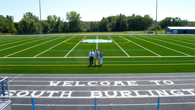 Interim Principal Pat Phillips stands with Interim Assistant Principal Jim Abrams and Assistand Principal Lissa McDonald on brand new turf laid on the South Burlington High School football field.