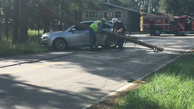 Linemen extract a car from a broken pole and severed power lines near the corner of  Wingfield and Chase streets Monday. The driver wasn't hurt in the crash, which only interrupted power to a couple of neighborhoods Aug. 11.