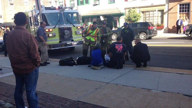 Police tend to an 11-year-old who was hit by a van in front of the courthouse in Gettysburg.