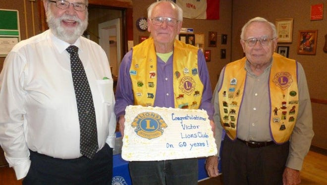 Officers with the Victor Lions Club hold up their anniversary cake. From left: David Heitmann, treasurer; Ivan Riggle, president; and Randall Betz, secretary.