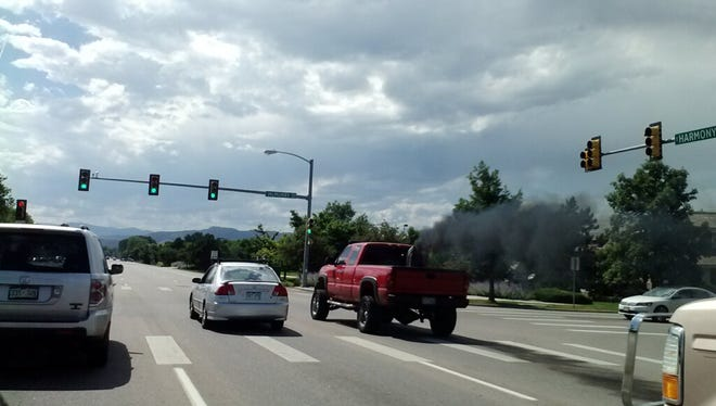 """Exhaust pours out of a truck driving on Harmony Road in south Fort Collins. Rep. Joann Ginal will again introduce legislation to stop so-called """"rolling coal"""" like this."""